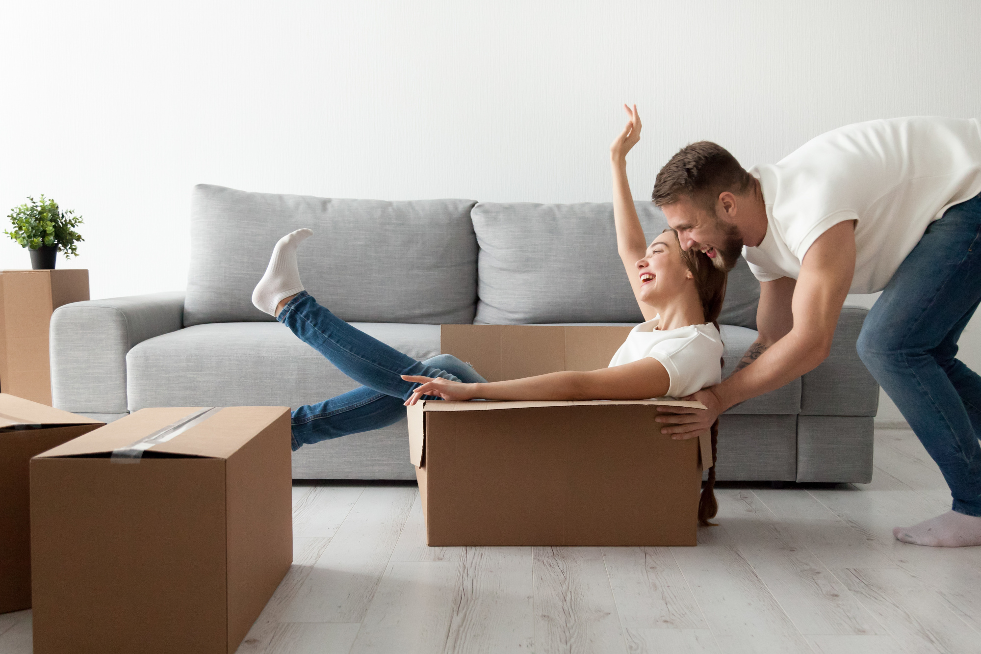 Happy couple having fun playing with cardboard box moving in